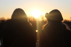 Silhouettes of two girls in front of sunset.