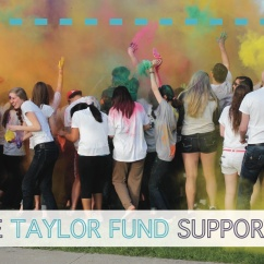 "Front of Taylor Fund mailer, with picture of students throwing colored powder. Text reads, ""100% of the Taylor Fund supports students."""